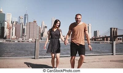 Smiling Caucasian couple walk away from epic New York view...