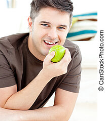Smiling caucasian man holding an apple looking at the camera