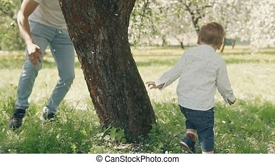 Smiling caucasian parents walking with son in summer apple tree park