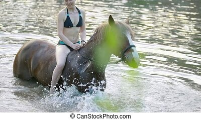 Smiling caucasian woman ride on the horse in the river at...