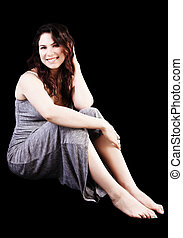Smiling Caucasian Woman Sitting In Grey Dress On Black Background