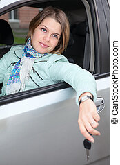 Smiling Caucasian woman sitting in land vehicle with car key