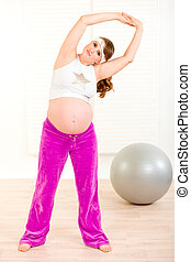 Smiling charming pregnant woman doing exercise at home