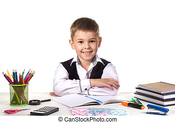 Smiling cheerful excellent pupil sitting still at the desk with white background