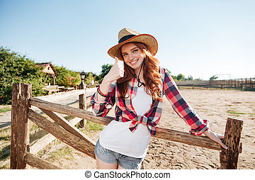 Smiling cheerful redhead cowgirl in hat showing thumbs up...