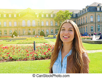 Smiling cheerful young woman in front of Neues Schloss (New Palace) of Stuttgart, Germany.