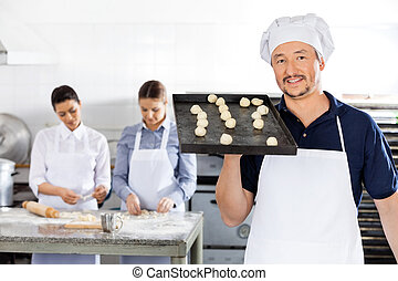 Smiling Chef Carrying Baking Sheet With Dough Balls At Kitchen