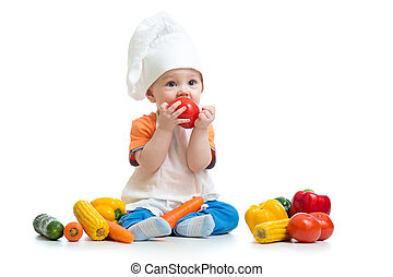 Smiling chef kid boy with vegetables isolated on white background