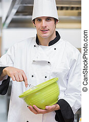Smiling chef mixing with whisk