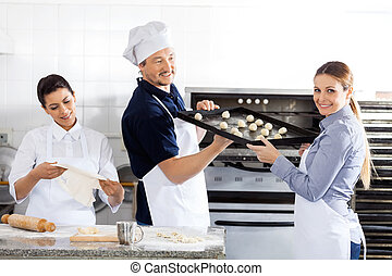 Smiling Chef Passing Baking Sheet To Colleague In Kitchen
