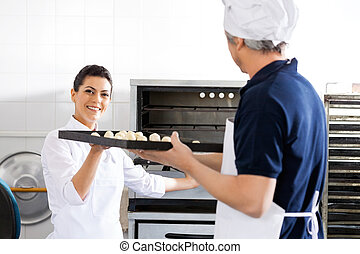 Smiling Chef Taking Baking Sheet From Colleague In Kitchen