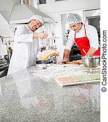 Smiling Chefs Cooking Ravioli Pasta Together In Kitchen