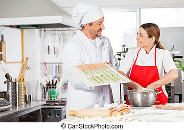 Smiling Chefs Preparing Ravioli Pasta In Kitchen