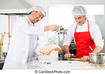 Smiling Chefs Preparing Ravioli Pasta Together In Kitchen