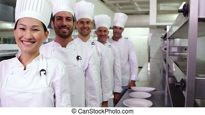 Smiling chefs standing in a row giving thumbs up in a...