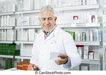 Smiling Chemist Holding Medicine At Counter In Pharmacy