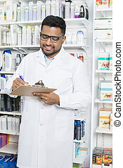 Smiling Chemist Writing On Clipboard In Pharmacy