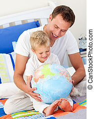 Smiling child and his father looking at a terrestrial globe