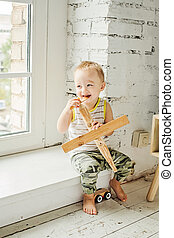 Smiling child boy having fun with at home. Small Kid playing wooden plane toy