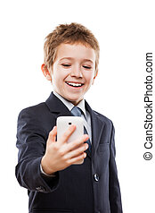 Smiling child boy in business suit holding mobile phone or smart