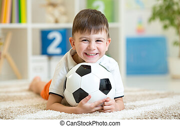 child boy with football at home