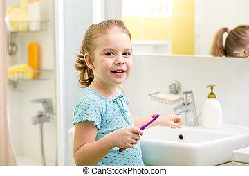Smiling child brushing teeth in bathroom