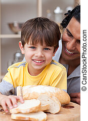 Smiling child eating bread with his father