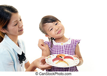 smiling child eating sushi