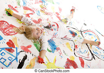 smiling child full of paint is laying on a painted floor