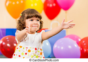 smiling child girl with balloons on birthday party