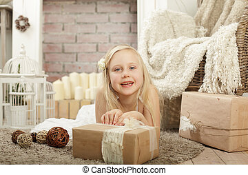Smiling child girl with gift box at provence style home