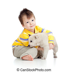smiling child hugging a puppy