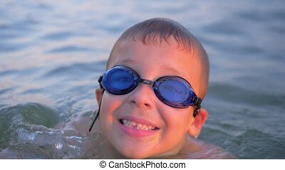 Smiling child in goggles swimming in the sea