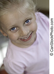 Smiling child looks into camera