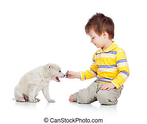 smiling child playing with a puppy
