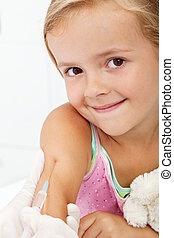 Smiling child receiving vaccine - healthcare concept, closeup