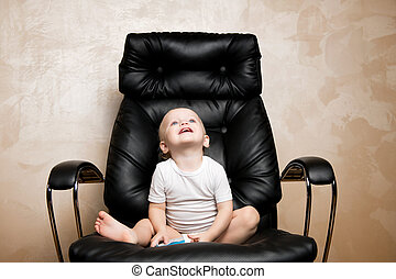 smiling child sitting in a large office chair