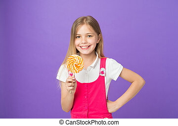 Smiling child with bright lollipop. Girl with long blond hair in pink outfit isolated on purple background. Sweet tooth with happy face holding big round candy, dessert time concept