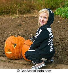 smiling child with Halloween pumpkin Jack O'Lantern