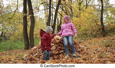 Smiling children jumping in pile of autumn leaves