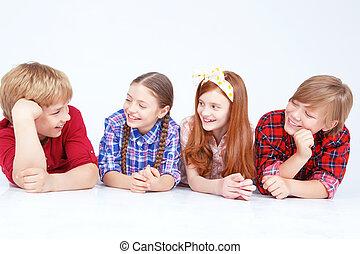 Smiling children lying on the floor in raw