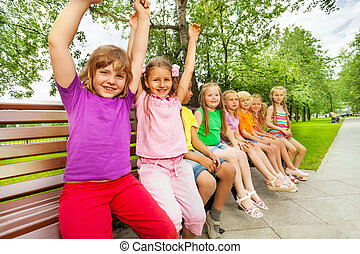 Smiling children sit in row on the bench