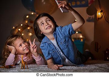 Smiling children taking selfie together in nursery