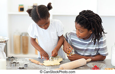 Smiling childrens cooking biscuits in the kitchen