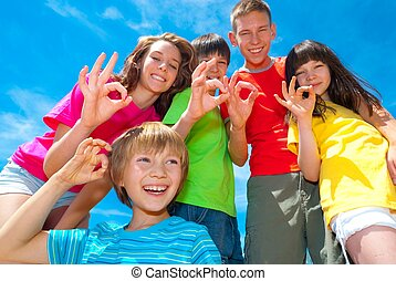 Group of five happy children of different ages all giving an okay sign, taken from a low perspective, with a blue sky background.