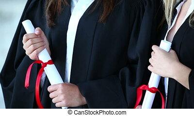Smiling classmates holding their diplomas