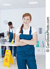 Smiling cleaner in office - Smiling young cleaner standing...