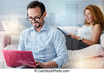 Smiling clever man working while a cheerful woman sitting behind him