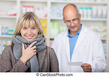 smiling client with scarf in pharmacy with pharmacist in...