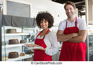 Smiling co-workers posing with desert at the bakery